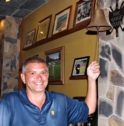 Medal winner Mark Reid rings the bell back at The Golf Club.