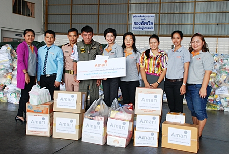 """The """"Friends in Need (of """"PA"""") Volunteers Foundation"""" led by Supanee Wangteerapong, CSR team leader of Amari Orchid Pattaya (5th right) met with officers of the Royal Thai Navy at U-Tapao airport to donate needed items to be delivered to people affected by the heavy floods."""
