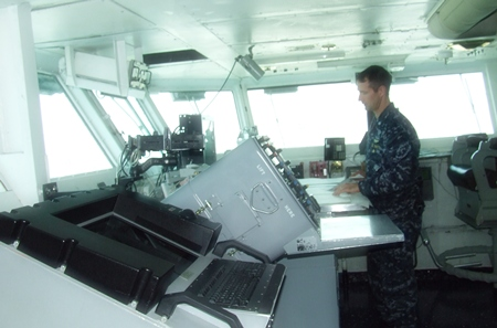 A naval officer goes about his business in the USS Abraham Lincoln control room.