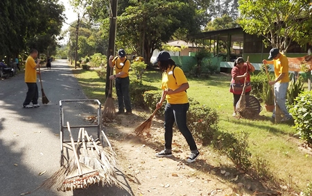 Sailors take time to rake leaves and clean up the grounds around the Banglamung Home for the Elderly.