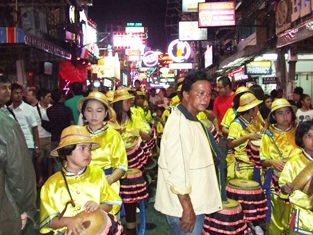Young long drummers prepare to march through Walking Street.