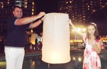 Father and daughter prepare to set free a khomloy (Chinese floating lantern) at the Montien Hotel.
