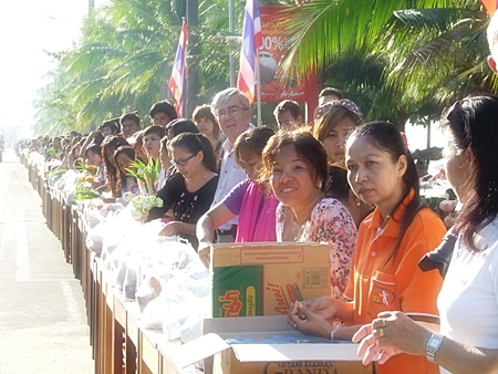 Thousands of residents line Jomtien Beach Road offering alms to monks and having lustral water sprinkled on them.