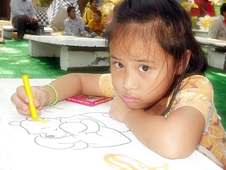 """This little one is coloring inside the lines during one of the many activities held throughout Pattaya for this year's Children's Day.  Prime Minister Yingluck Shinawatra advised Thailand's children to obtain """"Unity, knowledge, and wisdom, whilst preserving Thai identity and learning technology"""" in her message to children on this special day."""