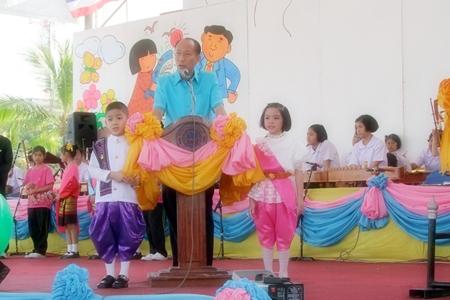 "Chonburi Gov. Khomsan Ekachai recites the Prime Minister's message of ""Unity, knowledge, and wisdom, whilst preserving Thai identity and learning technology"" at Chonburi's grand Children's Day celebrations."