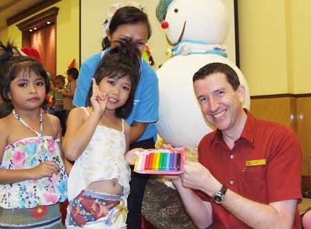 Michael Delargy (right), Sheraton Pattaya Resort general manager, hands out Christmas gifts to youngsters from the Seaton Center.