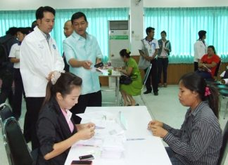 Banglamung District Chief Chawalit Saeng-Uthai (standing center) and Pattaya Mayor Itthiphol Kunplome (left) preside over the distribution of compensation for damage caused by local flooding in September and October.