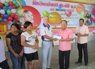 William Macy (3rd right), representing Pattaya Sports Club, presents a generous donation to Nongprue Mayor Mai Chaiyanit (2nd right) and Banglamung District Chief Chawalit Saeng-Uthai (right).