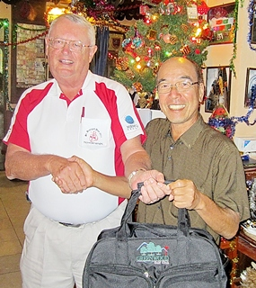 Dick Warberg (left) presents the MBMG Golfer of the Month award to Mashi Kaneta.