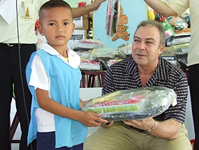 Thai Garden Resort General Manager Rene Pisters presents a gift package filled with much needed supplies to this grateful youngster.