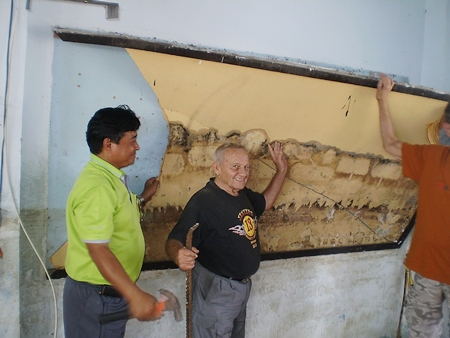 Bernie and the school principal take part in a small ceremony by removing the first damaged wall board to celebrate the beginning of the project.