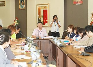 Mayor Itthiphol Kunplome (seated, center) chairs a meeting on AIDS prevention.
