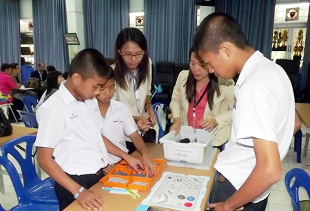 Teachers and students begin the process of learning how to assemble a robot.