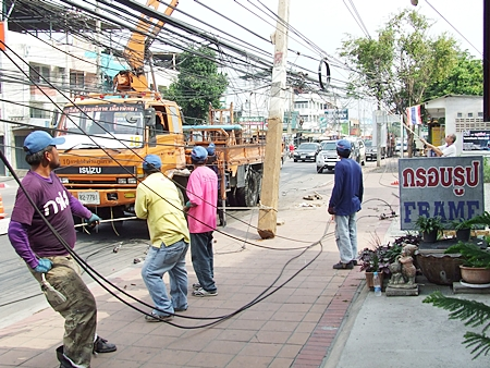 Provincial Electrical Authority workers erect a new utility pole in Naklua, one of a string of 11 leaning and crooked utility poles being replaced between Naklua sois 23 to 29.