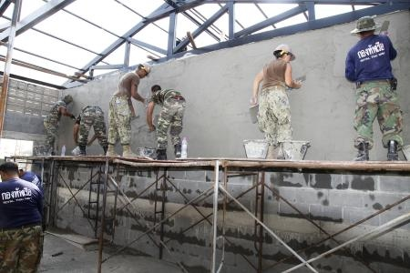 Royal Thai Navy, Malaysian forces and U.S. Navy Seabees with Naval Mobile Construction Battalion 40 apply stucco to a wall of a multipurpose building at the Wat Chalheamlap Temple School as part of Exercise Cobra Gold 2012, in Chonburi, Feb. 1. (Photo by Lance Cpl. Carl Payne)