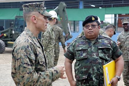 U.S. Marine Corps Lt. Col. Brian Clemens, deputy commanding officer, Combined Joint Military Operations Task Force, Navy Mobile Construction Batallion 40, left, speaks with Royal Thai Army Col. Chaimongkol Pralomram, right, at the Wat Chalheamlap School in Chonburi. (Photo by Cpl. Jessica Olivas)