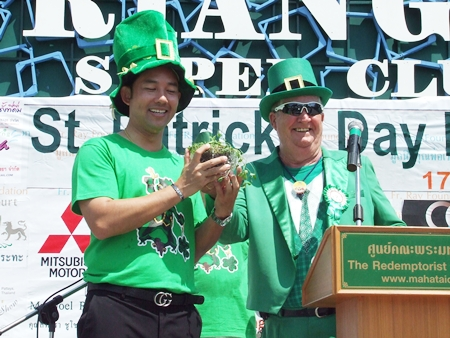 Mayor Itthiphol Kunplome (left) happily accepts a pot of 3-leaf clovers from Derrick Kane, grand marshal of the festival.