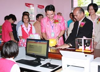 Mayor Itthiphol Kunplome breaks out his piggy bank to show students at Pattaya School No. 3 how to open a savings account.