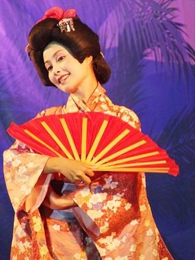 A beautiful geisha performs an enchanting fan dance.