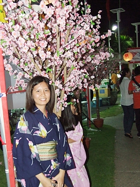 A woman poses next to cherry blossoms, which bloom beautifully in Japan in the springtime.