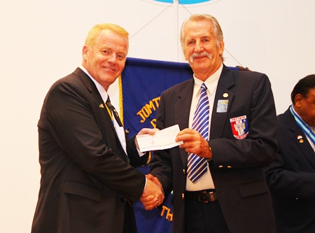 William Macey presents a cheque to President Gudmund to support the club's humanitarian projects.