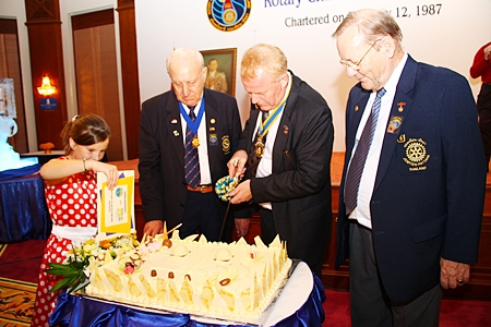 President Gudmund cuts the birthday cake, watched by PP Dennis Stark and PP Max Rommel.