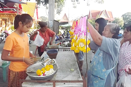 A young vendor prepares to sell her garlands so that people can make merit on Makha Bucha Day.