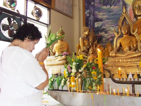 Lighting candles and making an offering to Buddha at Wat Nong - Or, Central Pattaya early morning on Makha Bucha Day.