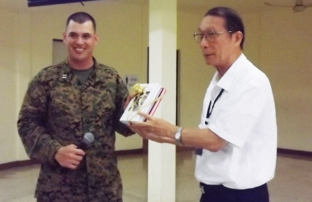 Chaplain Barrett Craig (left), Combat Logistics Battalion 31 accepts souvenir books from Father Veera Phangrak, director of the Pattaya Orphanage.