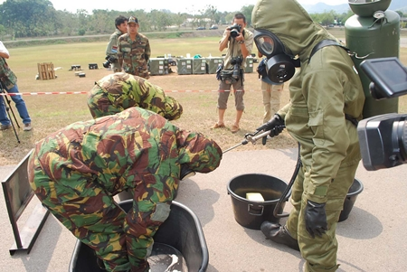 Troops are given a thorough washing after handling toxic chemicals.