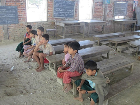 Barefoot children sit on old wooden benches, their toes making lines in the dirt floor.