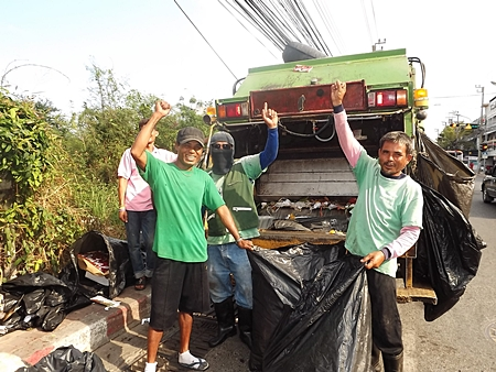 Somjit and fellow garbage collectors at work, picking up refuse to be carted away.