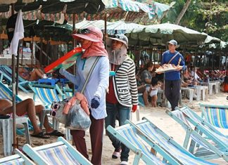 Vendors try to sell their wares to tourists on the beach.