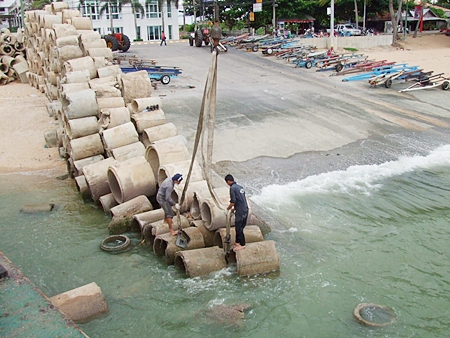 Workers prepare to load the concrete pipes onto a barge, which were then brought out to sea to become new homes for fish and coral.