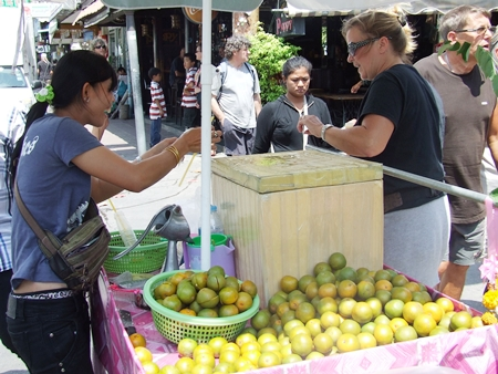 Namthip Mankhong sells a happy customer a cool refreshing orange juice.