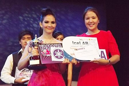 Phathakan Samertwet (left) from Pattaya School No. 11 receives her prize for winning the Thai or International singing category for teenagers, from Darin Phanthusak, director of Siam Kolakarn School.