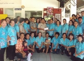 Naowarat Khakhay (standing, center right) presents a donation of 20,000 baht to Athapol Suriya representing the GFPD.