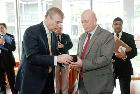 Graham MacDonald, president of the Royal British Legion Thailand presents Prince Andrew with a Legion Coin.