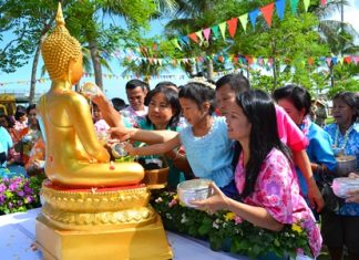Young and old gather to pour lustral water on the Buddha.