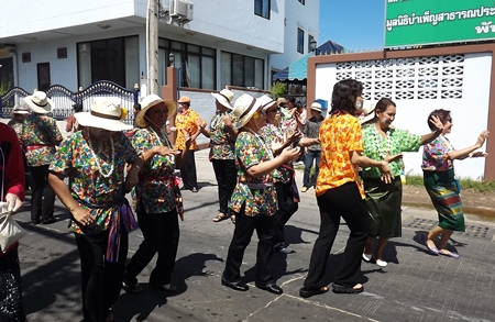 Women dressed in their best flowery blouses march in the Naklua parade.