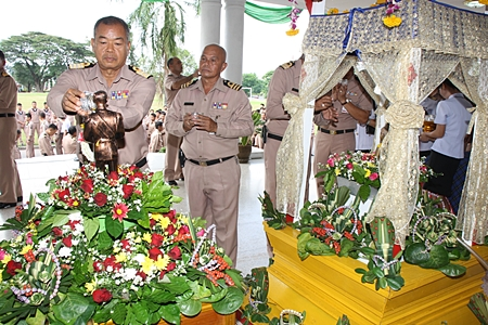 Navy officials and employees of Sattahip Naval base pour water on a Buddha statue and a statue of the Father of the Thai Navy, to celebrate Songkran.