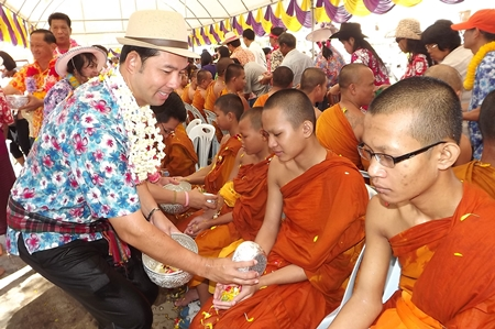 Mayor Itthiphol Kunplome pours lustral water on young monks at Wat Chaiyamongkol in South Pattaya.