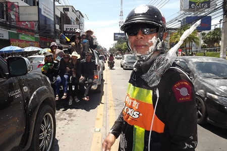 Officers work hard to help clear traffic even though they are often targets of water and powder during Wan Lai Pattaya.