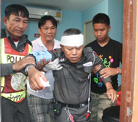 Traffic cop Sudsakhorn Changpim is helped through emergency care after he was attacked.