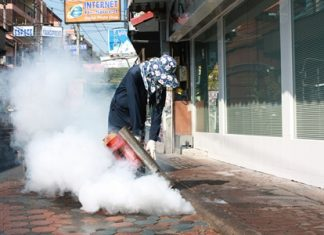 Sahas Wattanawiphat sprays insecticides to kill mosquitoes to combat dengue fever and malaria.