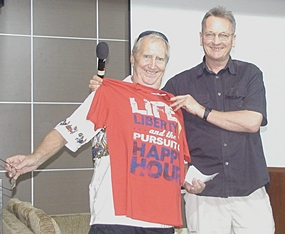 Open Forum host John Lyneham, a PCEC old timer just back in town for a short time, shows off a gift of a T-shirt to Hawaii Bob which could be a Pattaya motto; 'Life, Liberty and the pursuit of Happy Hour'.