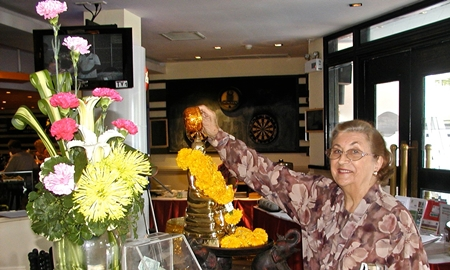 Arriving at the Pattaya City Expats Club's annual Songkran celebration, member Marjorie performs the 'washing of the Buddha'.
