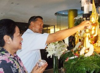 Gen Kanit Permsub and Khunying Busyarat pour lustral water on the sacred Buddha image.