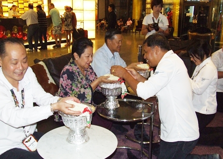 Staff of the Hard Rock Hotel pour scented water and receives blessings from Patrick Ng (left) and Gen Kanit Permsub and Khunying Busyarat.