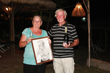Malcolm celebrates with a bottle of bubbly while wife Norma holds the pencil sketch presented by the Royal Varuna Yacht Club to mark his amazing swim.